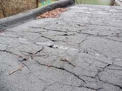 Garage roof with cracks all over that looks more like a lava field than an actual roof found by Keystone Home Inspections